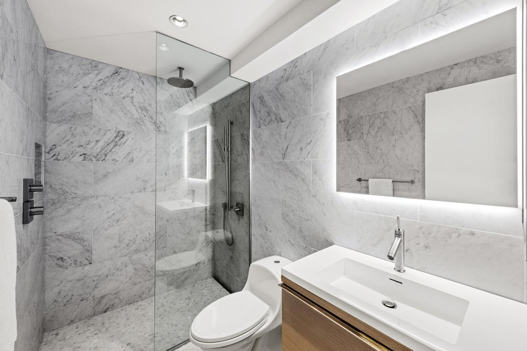 A one-of-a-kind triplex penthouse boasting a pair of rooftop terraces, this 3-bedroom, 4.5-bathroom condo is a remarkable contemporary city luxury and classic SoHo charm. Features of this palatial home include gorgeous hardwood floors, exposed steel beams and brick walls, soaring 18-ft ceiling, several chic built-ins and sky lights, central heating and cooling, a floating spiral staircase, built in home office/library, gas-burning fireplace, a convenient in-unit laundry room, and a flexible layout with the possibility of adding another bedroom.Beyond a tasteful foyer adorned with a walk-in coat closet and a pristine powder room, the lower level of the home flows into an expansive, open-concept living room, dining room, and kitchen saturated with natural light. The living and dining spaces have an incredible double-height ceiling and wraparound exposed brick walls, while the kitchen is equipped with an eat-in peninsula, sleek white countertops, an exposed brick backsplash, custom cabinets, and a suite of high-end stainless steel appliances from Viking, Wolf and Sub Zero. Completing the lower level is a secluded, sky-lit media room with a gas-burning fireplace and a wet bar. The media room can easily be converted into a fourth bedroom.The second level of the home contains a pair of spacious bedrooms that overlook the living space below. The master bedroom possesses a cavernous walk-in closet, an additional reach-in closet, and an immaculate en-suite bathroom with a walk-in shower and a deep soaking tub. The second bedroom has a private closet and a beautiful en-suite bathroom. The third bedroom sits on the upper level of the home and has a private en-suite as well as direct access to a tranquil lower terrace with a grill and lush planters. The upper terrace has a copper pergola, built-in lighting, and stylish lounge furniture with outdoor grill perfect for true indoor-outdoor living in the heart of SoHo.131 Mercer Street is an impeccable boutique condominium originall